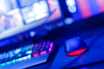 Professional computer mouse for video games and cyber sports on background of monitor, neon color