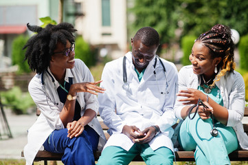Three African American group doctors with stethoscope wearing lab coat sitting on bench.