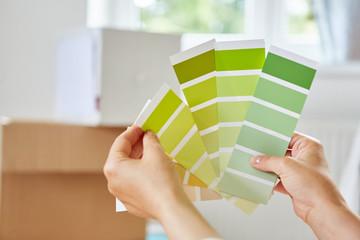Frau bei Auswahl der Wandfarbe mit Farbpalette