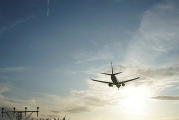 Landing aircraft at the airpot at sunset Fotobehang