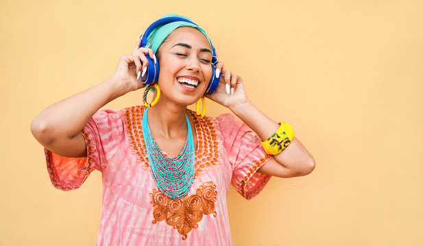 Young african woman listening music with headphones device - Happy girl having fun dancing and singing outdoor - Lifestyle, stylish and technology concept - Focus on face