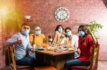 Indian family wears face mask while eating food in restaurant after corona pandemic unlock - concept showing new normal lifestyle in India