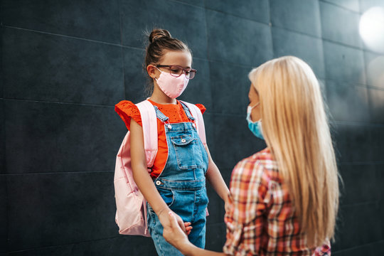 Young mother walking with her little daughter to elementary school. They wearing face protective masks. Back to school concept.