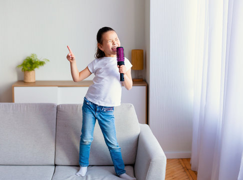 Chinese Little Girl Singing Holding Hairbrush Like Microphone At Home