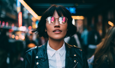 Caucasian woman in optical spectacles with neon reflection of lights standing at urbanity during...