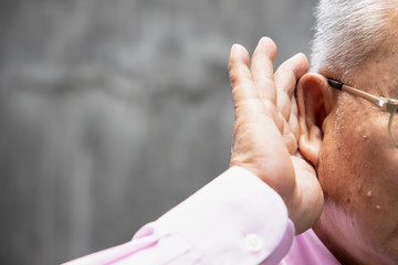 Asian senior man listening to something; portrait of old asian man with hearing ear, concept of rumor, gossip, hearing loss, hard of hearing, fake news, bad news, good information