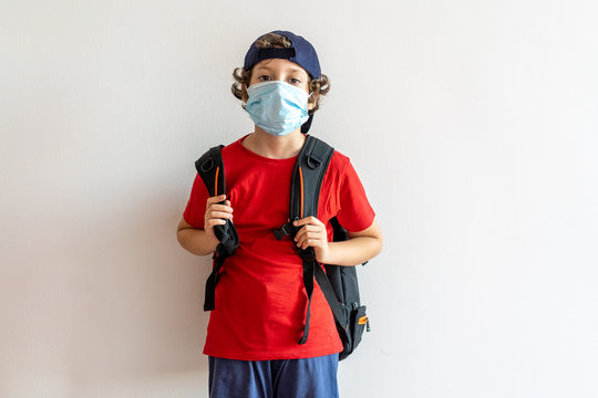 Little boy, elementary school student, going to school with a backpack. New normality at coronavirus, covid-19, time wearing a safety mask. School reopening concept.