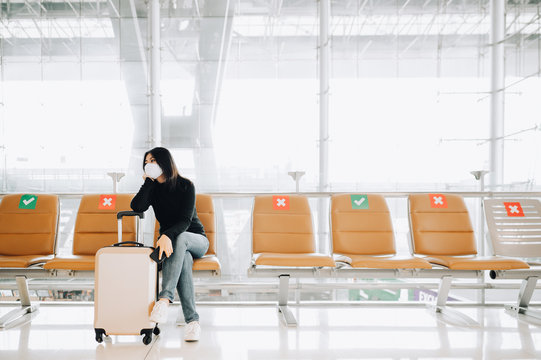 Asian woman tourist wearing face mask sitting on social distancing chair with luggage waiting for flight at airport terminal during coronavirus or covid-19 outbreak . New normal travel at airport