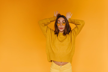 Positive tanned girl in sunglasses making funny faces on orange background. Indoor portrait of cheerful brown-haired woman wears orange sweater. Wall mural