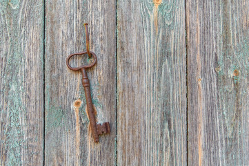 An old iron retro key hanging on a nail against the wall of a rustic wooden house, the concept of a secret, inheritance, opportunity.