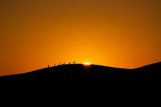 panorama dell'alba nel deserto marocchino di merzouga, con persone sullo sfondo stagliate contro il sole che sorge