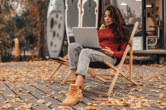 Beautiful woman in cozy outfit works at laptop while sitting on chair near cafe in autumn park.