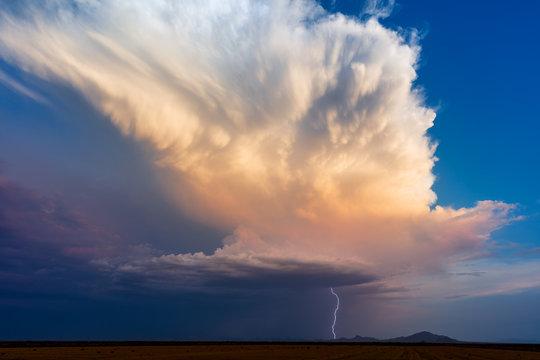 Thunderstorm cumulonimbus cloud with lightning and blue sky at sunset