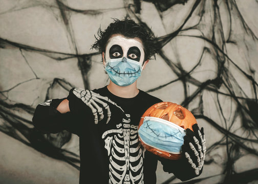 Happy Halloween,kid wearing medical mask in a skeleton costume with halloween pumpkin