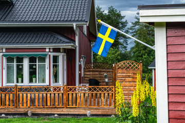 Front view of traditional Swedish wooden red house with summer terrace at countryside. Swedish flag at right side, mounted on small guest house, summer day just after rain. Flowers, blurry forest.
