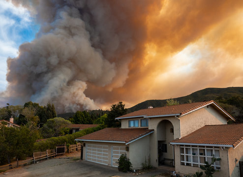 """The California """"River Fire"""" of Salinas,  in Monterey County, was ignited by dry lightning on August 16, 2020, fills the sky with dark smoke and flames as it burns close to a houses on its first day."""