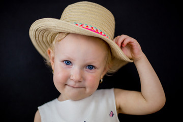 little girl on a black background with an imaginary facial expression, blue eyes and blonde hair