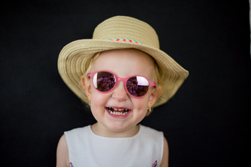 little girl on a black background with glasses on her eyes, a sincere childish smile on her face and blonde hair