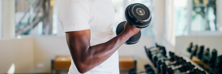 Young African American man standing and lifting a dumbbell with the rack at gym. Male weight training person doing a biceps curl in fitness center