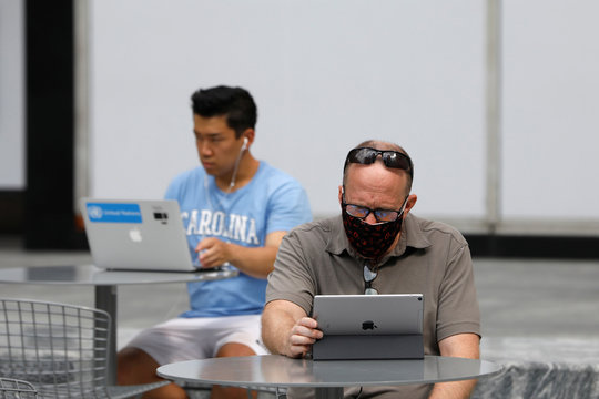 People use an Apple laptop computer and an Apple iPad in Manhattan, New York City