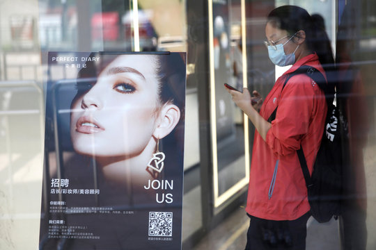 A woman wearing a face mask stands next to a recruiting advertisement inside a Chinese cosmetics brand Perfect Diary store, following the coronavirus disease (COVID-19) outbreak  in Beijing
