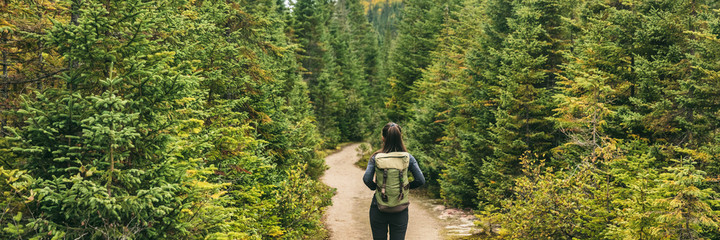 Wall Mural - Autumn hiker woman hiking in forest nature panoramic background. Travel outdoors girl going camping in Canada banner.