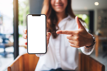 Door stickers Wall Decor With Your Own Photos Mockup image of a beautiful woman pointing finger at a mobile phone with blank white screen