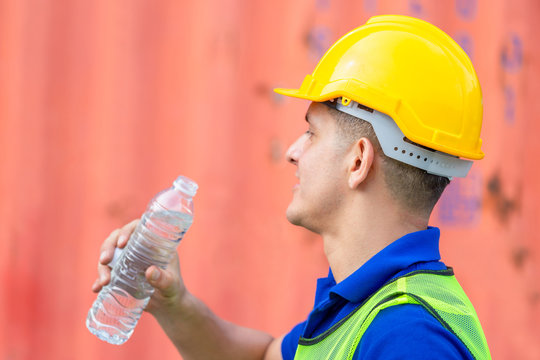 Close up of Worker man in hard hat drinking water at containers cargo