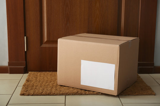 Parcel on rug near door. Delivery service