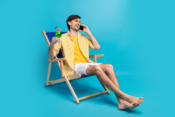 Dude i paradise. Full length photo man relax rest resort sit chaise-lounge drink cocktail call friend tell weekend wear white yellow shirt shorts barefoot isolated blue color background