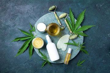 Hemp leaves, oil, cosmetic products, face cream, body butter, face roller and gua sha massager on dark background. Top view, copy space. Natural skin and self care concept. Flat lay. Banner.