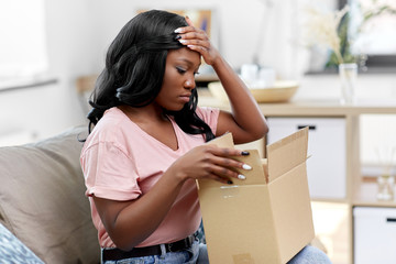 delivery, shipping and people concept - young african american woman opening parcel box at home and...