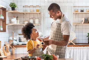 African American Father and son laughing while cooking in kitchen