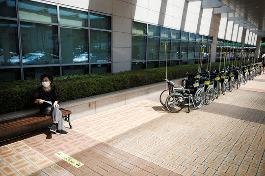 A woman wearing a mask to avoid the spread of the coronavirus disease (COVID-19) rests near wheelchairs for patients at a hospital in Seoul
