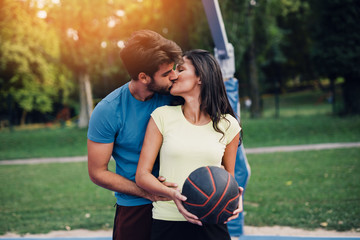 Beautiful young couple kissing and enjoying together and playing on basketball court. Bright sunny...