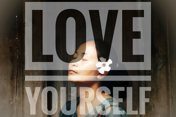 Love yourself motivational concept on background of Asian woman face, eyes closed with a white flower on ear. Spa still life concept. Women's day concept. Self awareness and confidence concept.