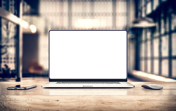 Laptop with frameless blank screen mockup template on table in industrial office loft interior - front view