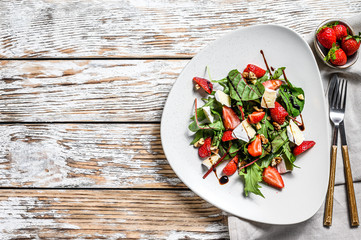 Fototapeta Salad with Camembert, strawberries, nuts, chard and arugula. White background. Top view. Copy space