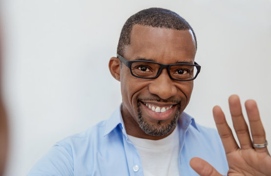 Portrait of young handsome black African man use smartphone selfie say hi over white background. Happy afro guy online influencer blogger. Education technology connected people man lifestyle concept