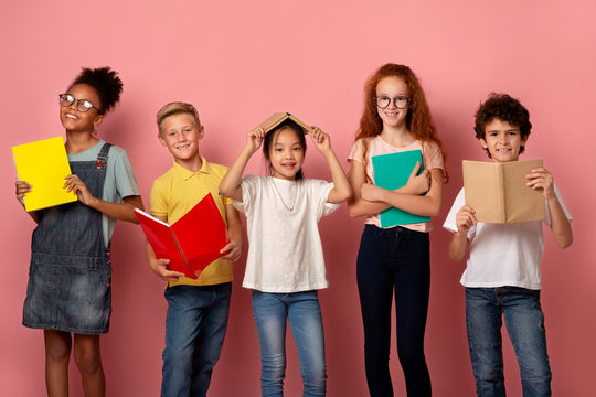 School education. Portrait of smiling diverse kids with books and copybooks looking at camera, pink background