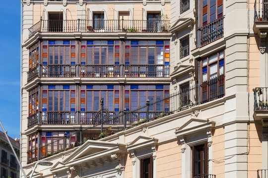 Details of the one of old buildings with colored glasses in modern style in the historical center of Barcelona in sunny day. Spain.