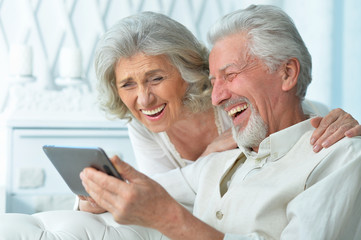 Close up portrait of happy senior couple using tablet