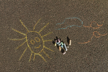 simple chalk drawing of smiling sun, clouds and birds on the pavement