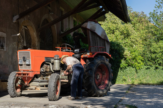 Old farmer working on red tractor under roof of farmer house in sunshine.