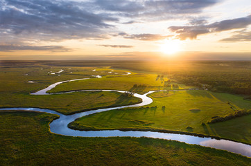 Aerial sunset view to green land and river in summertime