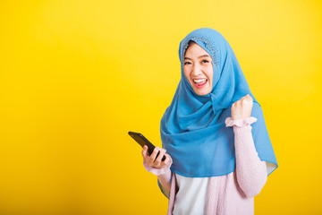 Asian Muslim Arab, Portrait of happy beautiful young woman Islam religious wear veil hijab funny smile she raise hand glad celebrating winning with smart mobile phone isolated on yellow background