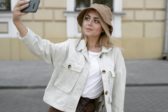 tourist woman in a European city, tourism in Europe. young girl dressed in a Panama hat makes a selfie on her phone. Tourism and couchsurfing