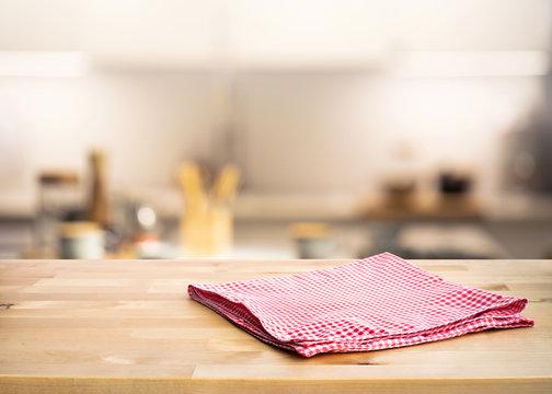 Red fabric,cloth on wood table top on blur kitchen counter (room)background