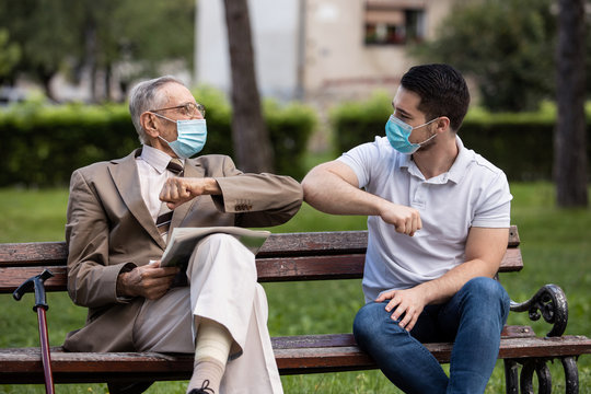 Two generations, grandfather and grandson talking under covid masks in the park