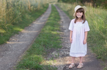 Photo sur Plexiglas Doux monstres Little girl in a hat and white dress stands on a road near field of rye.